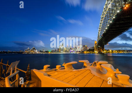Sydney Harbour, the Sydney Opera House and Circular Quay as seen from Milson's Point and the bow of HMAS Sydney. - Stock Photo