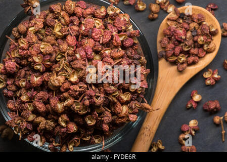 Szechuan Peppercorns in Glass Bowl with Spill Over in wooden spoon - Stock Photo