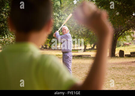 Grandparents spending time with grandson: Senior man playing baseball with his grandson in park. The old man holds - Stock Photo