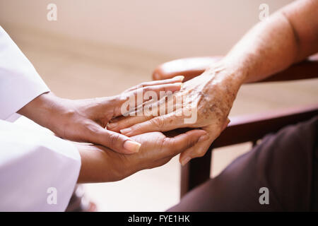 Old people in geriatric hospice: Aged patient receives the visit of a female black doctor. They shake their hands - Stock Photo