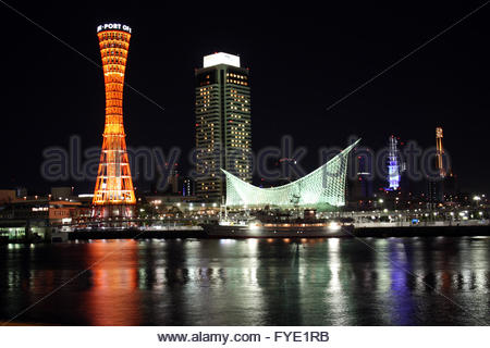 Kobe Port Tower and buildings at night from across harbor - Stock Photo
