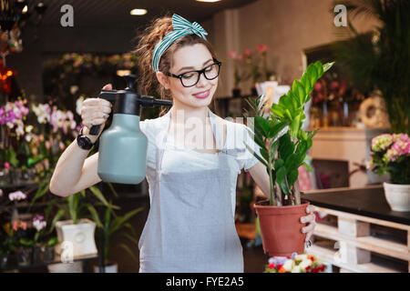 Happy beautiful young woman florist in apron watering plants with pulvelizer in flower shop - Stock Photo