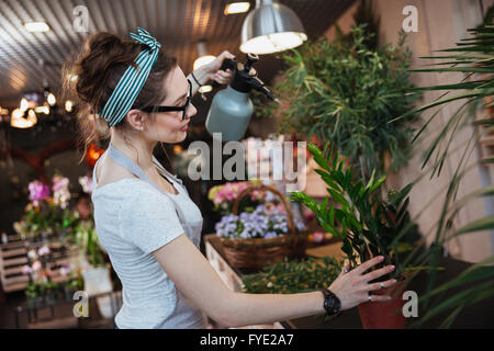 Smiling cute young woman florist standing and watering plants with water sprayer in flower shop - Stock Photo