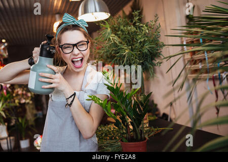 Funny pretty young woman florist watering flowers and pointing with water sprayer on you - Stock Photo