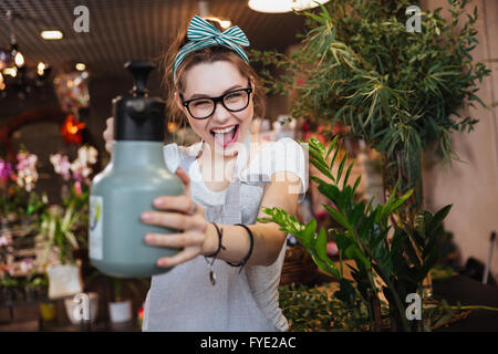 Playful attractive young woman florist pointing with water sprayer on you in flower shop - Stock Photo