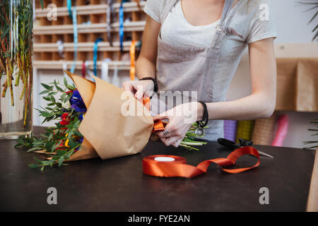 Hands of young woman florist standing and making bouquet of flowers in shop - Stock Photo