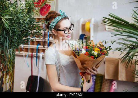Smiling attractive young woman florist standing and holding bouquet of flowers in shop