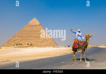GIZA, EGYPT - September, 16, 2008: Camel rider and Pyramid of Khufu, Giza, Egypt - Stock Photo