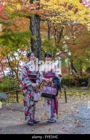 KYOTO, JAPAN - November, 18, 2014: Two japanese girls in traditional kimono, momiji season in Kyoto - Stock Photo