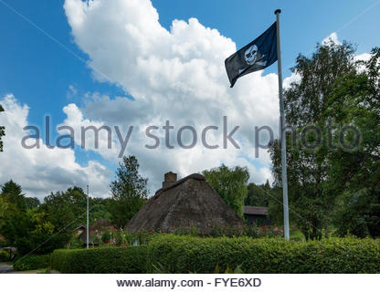 Skull and crossbones pirate flag flies on a pole by a thatch-roofed house in the Angeln region of Schleswig-Holstein, - Stock Photo