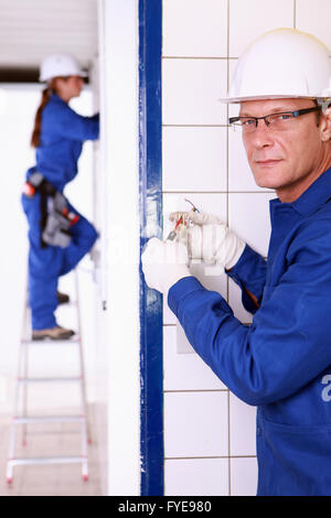 a male and female craftsman doing electricity works - Stock Photo