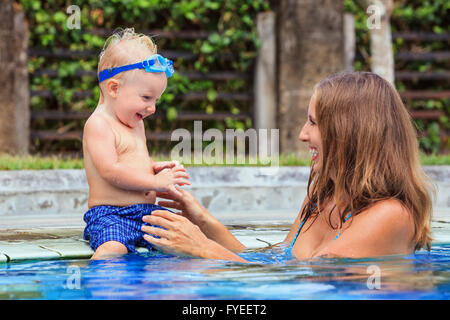 Little swimming child in underwater goggles sit on poolside, has fun - baby play with   smiling woman in pool. - Stock Photo