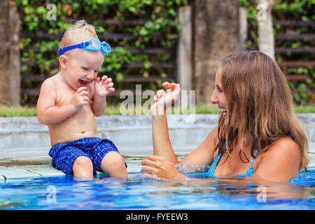 Little swimming child in underwater goggles sit on poolside, has fun - baby splashing with mother in pool. - Stock Photo