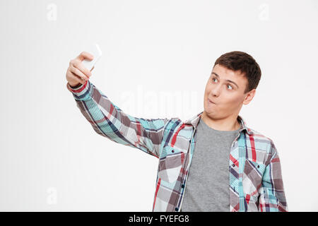 Funny man making selfie photo on smartphone isolated on a white background - Stock Photo