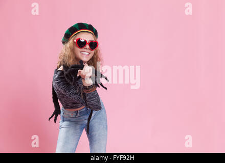 Funky portrait of a young woman wearing a wig hat. Studio shot with pink background. - Stock Photo