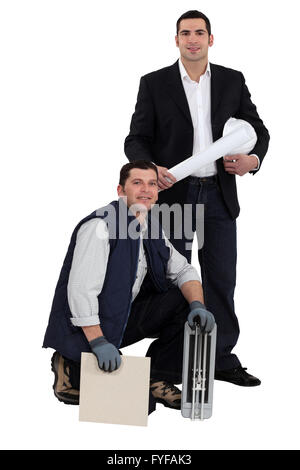 Portrait of an engineer and a workman holding a tile and a ceramic tile cutter - Stock Photo