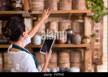 Tea house owner checking inventory using digital tablet - Stock Photo