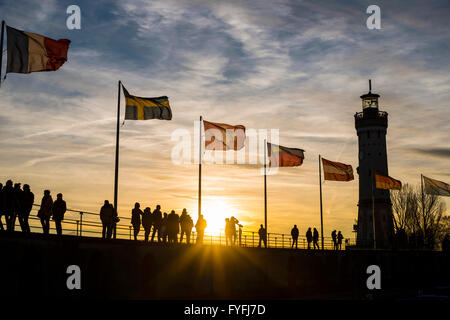 Silhouettes of people and flags at sunset, harbor in Lindau am Bodensee, Bavaria, Germany - Stock Photo