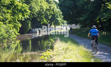 Leeds, England - June 30, 2015: Cyclists ride in the sunshine on the towpath of the Leeds and Liverpool Canal. - Stock Photo