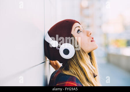 Half length profile portrait of young handsome caucasian blonde hair woman leaning against a wall, listening music - Stock Photo