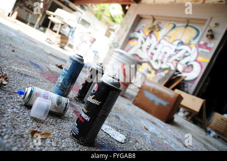 Cans of spray paint near a building that is littered with graffiti in Austin, TX - Stock Photo