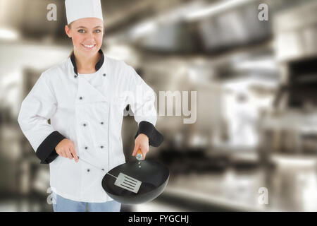 Composite image of portrait of chef using spetula and frying pan - Stock Photo