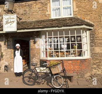 Young shopkeeper woman in old fashioned traditional clothing outside the village bakery shop, Lacock, Wiltshire, - Stock Photo