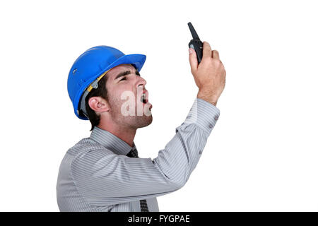 angry businessman wearing a helmet and shouting on his walkie talkie - Stock Photo