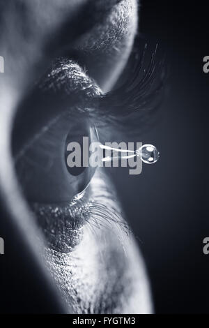 Eye health and vision concept. Pupil detail and tear water drop - Stock Photo
