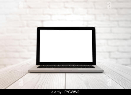 digitally generated laptop on a wooden table with blank screen - Stock Photo