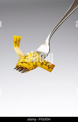 Fork with Tape Measure Dieting Concept Obesity - Stock Photo