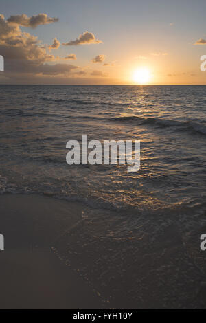 Beach sunset over the sea, view from coast with calm waves and sun in horizon. - Stock Photo