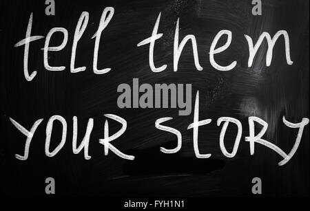 Tell them your story handwritten with white chalk on a blackboard - Stock Photo