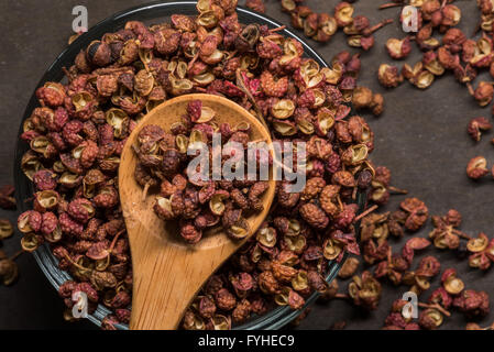 Szechuan Peppercorns in Wooden Spoon With Glass Bowl and spill over - Stock Photo