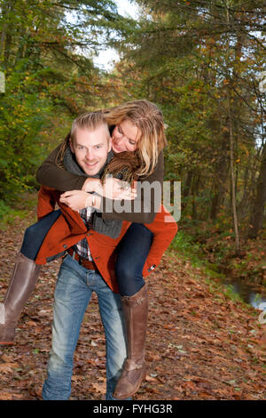 Young couple is riding piggyback - Stock Photo
