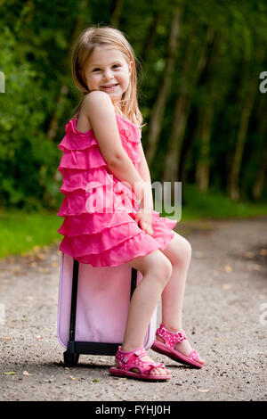 Little girl is sitting on her suitcase - Stock Photo