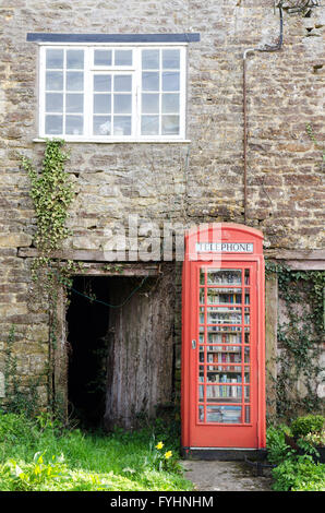 A classic British red phonebox in the small village of Ryme Intrinseca, Dorset, England, has been converted to a - Stock Photo