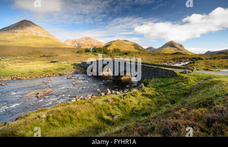 Old stone arch bridge over a mountain river at Sligachan on the Isle of Skye in the Highlands of Scotland. - Stock Photo