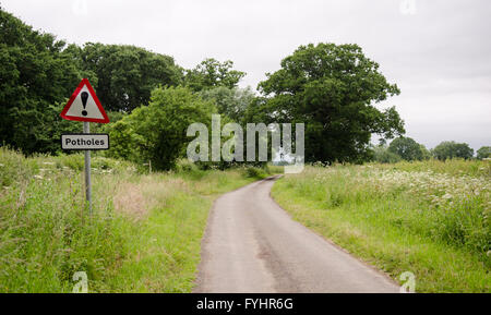 A sign beside a single track country lane road warning of potholes. - Stock Photo
