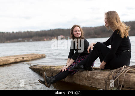Girls girlfriends sitting together near the river. - Stock Photo