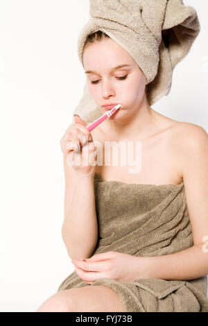 Young woman is brushing her teeth - Stock Photo