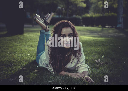 summer redhead girl with denim jacket lying on a park - Stock Photo