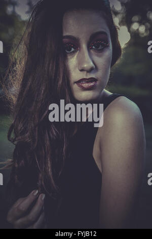 cute, redhead girl with black dress on a park - Stock Photo