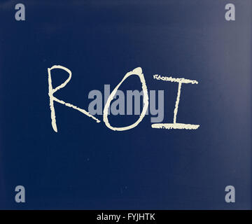 The word ROI handwritten with white chalk on a blackboard - Stock Photo