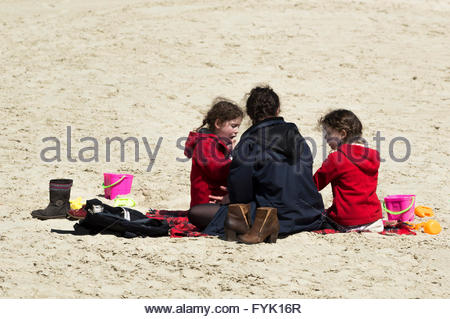 Women sitting on the sandy beach with two little girls, Lyme Regis, Dorset - Stock Photo