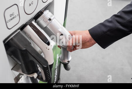 A man holds a DC CHAdeMO plug for electric vehicles next to a DC Combo 2 (L) and an AC plug, at the Hannover Messe - Stock Photo