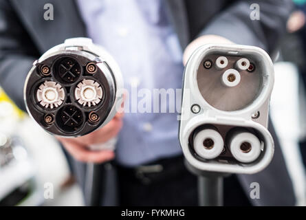 A man holds up a DC CHAdeMO plug (L) and a DC Combo 2 plug for electric vehicles, at the Hannover Messe industrial - Stock Photo