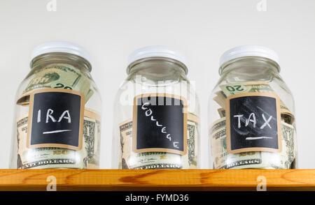 Three glass jars on wooden shelf for savings - Stock Photo