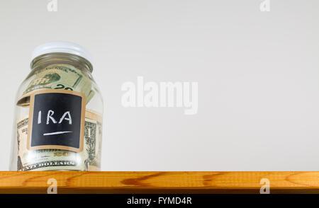 Single glass jar on wooden shelf for saving money - Stock Photo