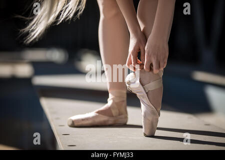 Dancer tying pointe shoes - Stock Photo